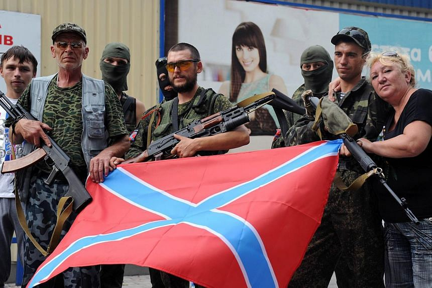 Pro-Russian militants posing with the new Russia flag in Donetsk, eastern Ukraine, on July 13, 2014. -- PHOTO: AFP