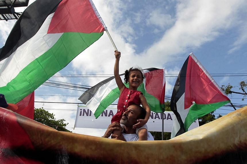 A girl holds a Palestinian flag during a march in Managua against Israel's military action in Gaza July 14, 2014. -- PHOTO: REUTERS