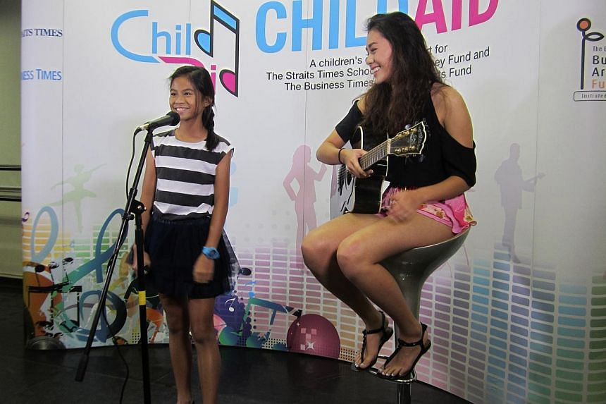 Seven-year-old Renee Yadav playing the harp and 11-year-old Micaela Rose Lai (left) singing with sister Erica Jane accompanying her on the guitar. -- ST PHOTO: ANG YIYING