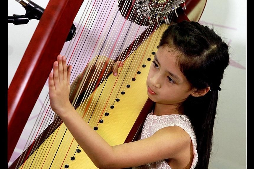 Seven-year-old Renee Yadav (above) playing the harp and 11-year-old Micaela Rose Lai singing with sister Erica Jane accompanying her on the guitar. -- ST PHOTO: LAU FOOK KONG