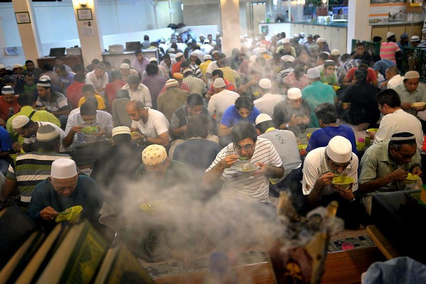 A group of men breaking fast together at Khalid Mosque in Joo Chiat Road in July 2014. -- PHOTO: THE NEW PAPER FILE