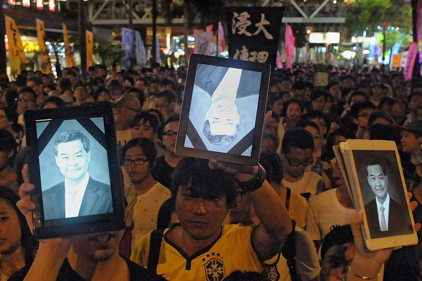 Protesters hold up tablet computers showing an image of Hong Kong's Chief Executive Leung Chun-ying at a pro-democracy rally seeking greater democracy in Hong Kong on July 1, 2014 as frustration grows over the influence of Beijing on the city. Hong K