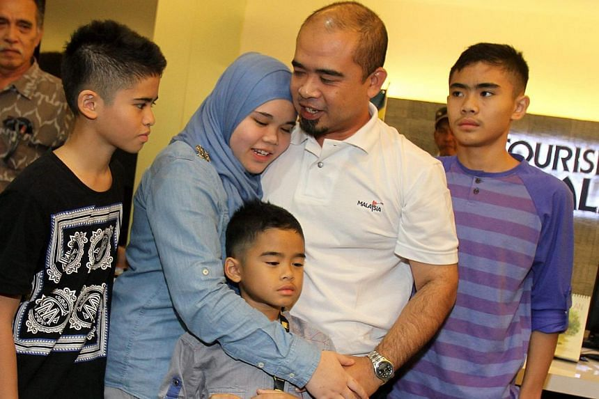 Mr Azizul Raheem Awaluddin reunited with his four children (from left) Adam, 11, Aishah 14, Arif, seven, and Ammar, 12, at the KL airport yesterday. -- PHOTO: THE STAR/ASIA NEWS NETWORK