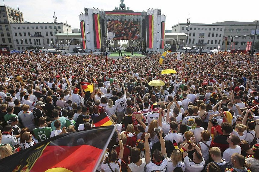 German soccer fans cheer as they wait for the arrival of their team, winners of the 2014 World Cup, near the Brandenburg Gate in Berlin,on July 15, 2014. Tens of thousands of jubilant Germany fans massed at Berlin's Brandenburg Gate on Tuesday awai