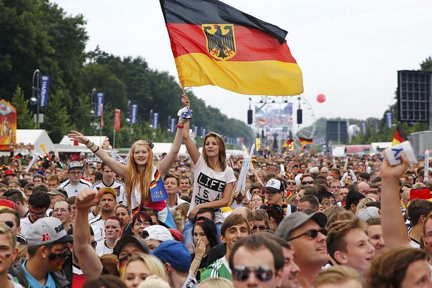 German soccer fans cheer as they wait for the arrival of their team, winners of the 2014 World Cup, at a public viewing zone called 'fan mile' in Berlin,on July 15, 2014. -- PHOTO: REUTERS