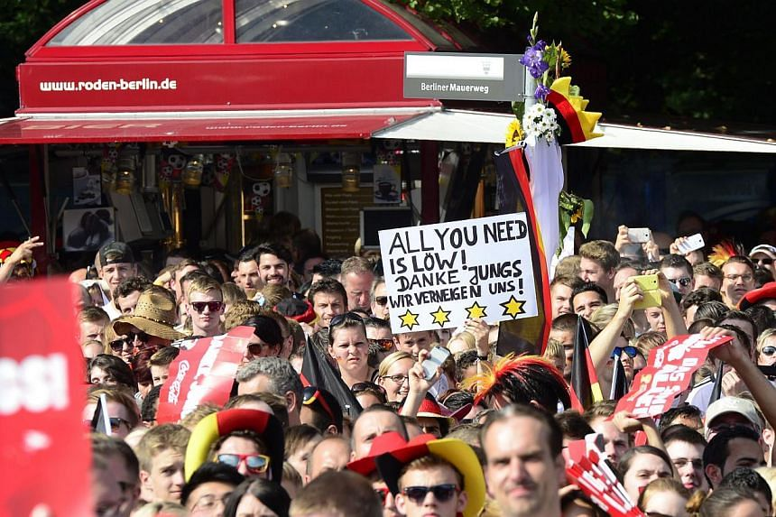 """A man holds a banner that reads """"All you need is Loew, thank you guys, we take a bow"""" as German fans gather in front of a stage installed for a victory parade of Germany's football national team on July 15, 2014 at Berlin's landmark Brandenburg Gate"""
