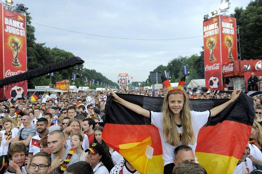 German fans gather on the 17th of June street in Berlin on July 15, 2014, few hours before the victory parade of German national football team at landmark Brandenburg Gate to celebrate their FIFA World Cup title. -- PHOTO: AFP