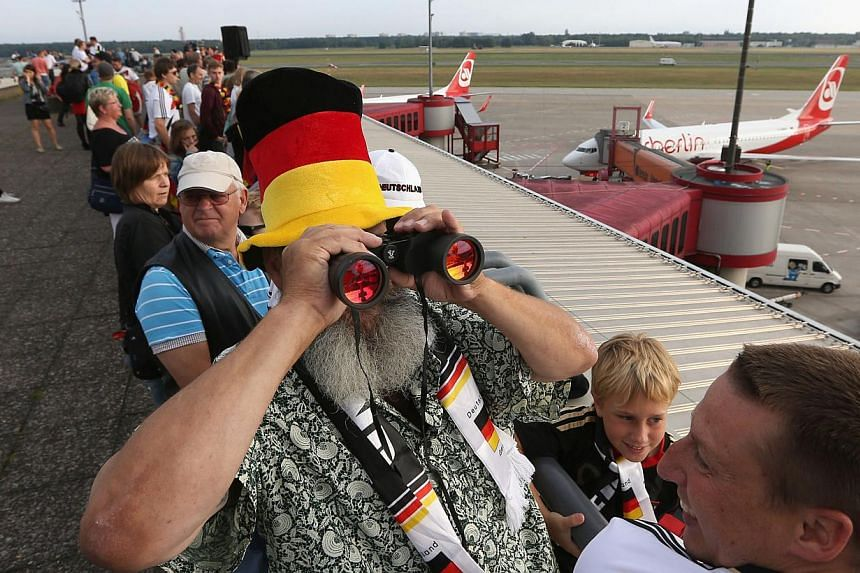 A German fan uses binoculars as he stands on the visitors terrace at Berlin airport Tegel on July 15, 2014, where the plane of German national football team is expected on their way back from Brazil after they won the FIFA World Cup 2014. -- PHOTO: A