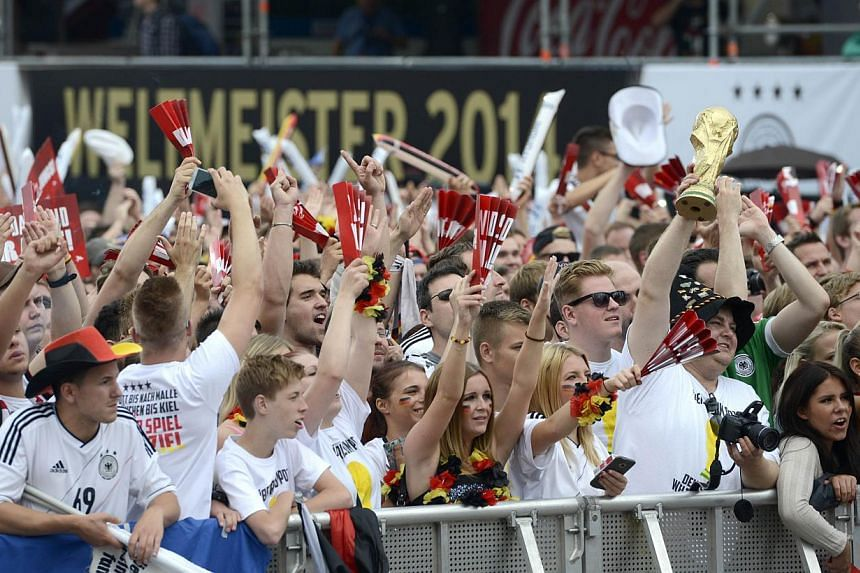 German fans wait in front of a stage installed for a victory parade of Germany's football national team on July 15, 2014 at Berlin's landmark Brandenburg Gate to celebrate their FIFA World Cup title. -- PHOTO: AFP