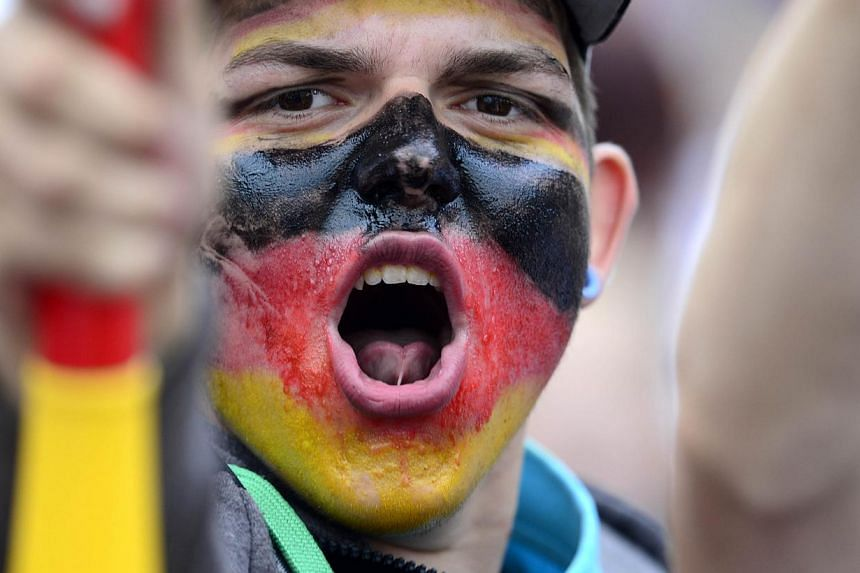 A German fan has his face painted with the German national colours as he waits in front of a stage installed for a victory parade of Germany's football national team on July 15, 2014 at Berlin's landmark Brandenburg Gate to celebrate their FIFA World