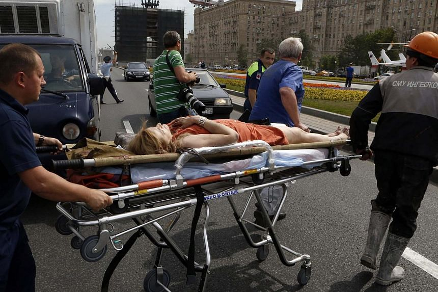 Members of the emergency services move an injured passenger outside a metro station following an accident on the subway in Moscow on July 15, 2014. Twelve people were killed on Tuesday and up to 120 injured when a Moscow underground train derailed be