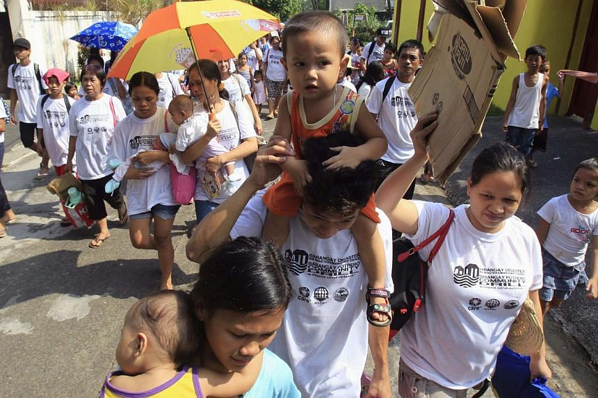 Residents carry children as they participate in a flood evacuation drill in Malabon City, north of Manila on June 7, 2014. The Philippines evacuated eastern coastal areas, suspended ferry services and closed schools in parts of the main Luzon island