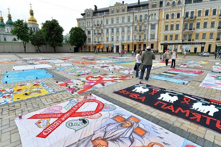 People gather on Saint Sophia square in Kiev to look at quilts embroidered with the names of AIDS victims during a ceremony to mark World Remembrance Day of AIDS Victims on May 18, 2014.Global Aids-related deaths and new HIV infections have fal