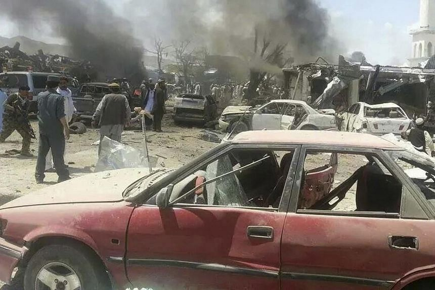 Villagers gather at the site of a car bomb attack in Urgon district, eastern province of Paktika on July 15, 2014.Afghan officials on Wednesday, July 16, 2014, began investigating a devastating suicide bombing at a busy market that killed at le