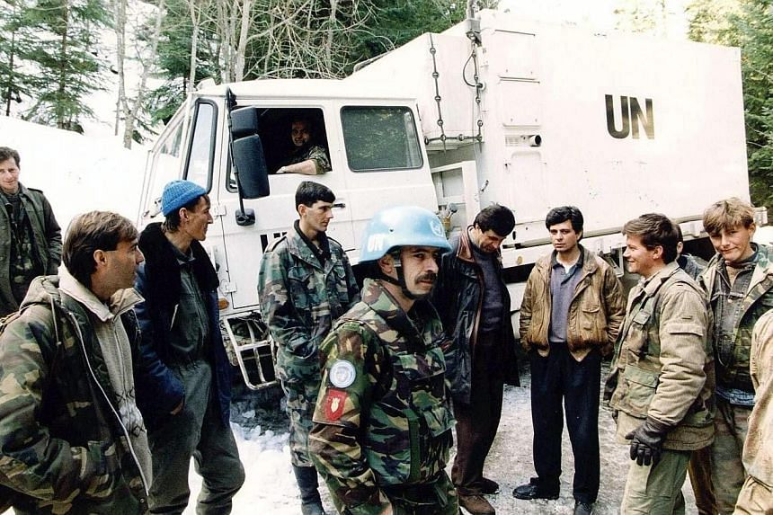 A file photo taken on March 1, 1994 shows Dutch soldiers of a Dutchbat convoy chatting with Bosnian Muslim fighters in Vares, Bosnia. A court in the Netherlands ruled Wednesday, July 16, 2014, that the Dutch state was liable for the deaths of o