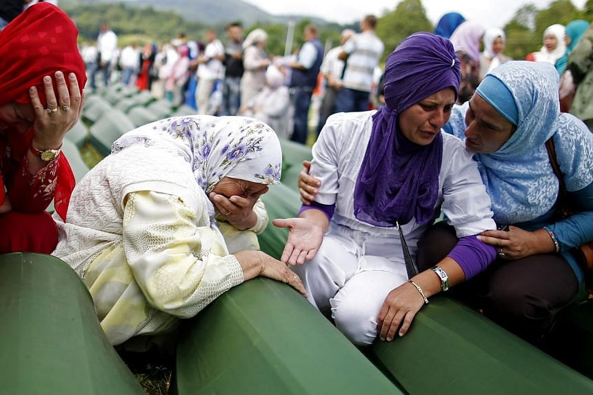 Bosnian Muslim women cry near the coffin of their relative, one of the 175 coffins of newly identified victims from the 1995 Srebrenica massacre, in Potocari Memorial Center, near Srebrenica on July 11, 2014. -- PHOTO: REUTERS