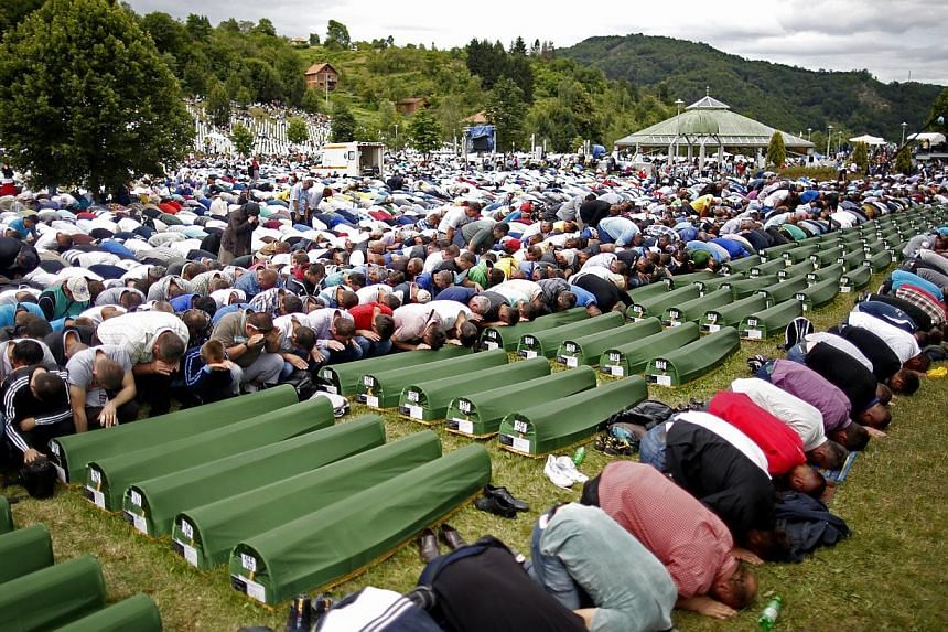 Bosnian Muslims pray during a mass funeral for 175 newly identified victims from the 1995 Srebrenica massacre, at Potocari Memorial Center, near Srebrenica on July 11, 2014. -- PHOTO: REUTERS