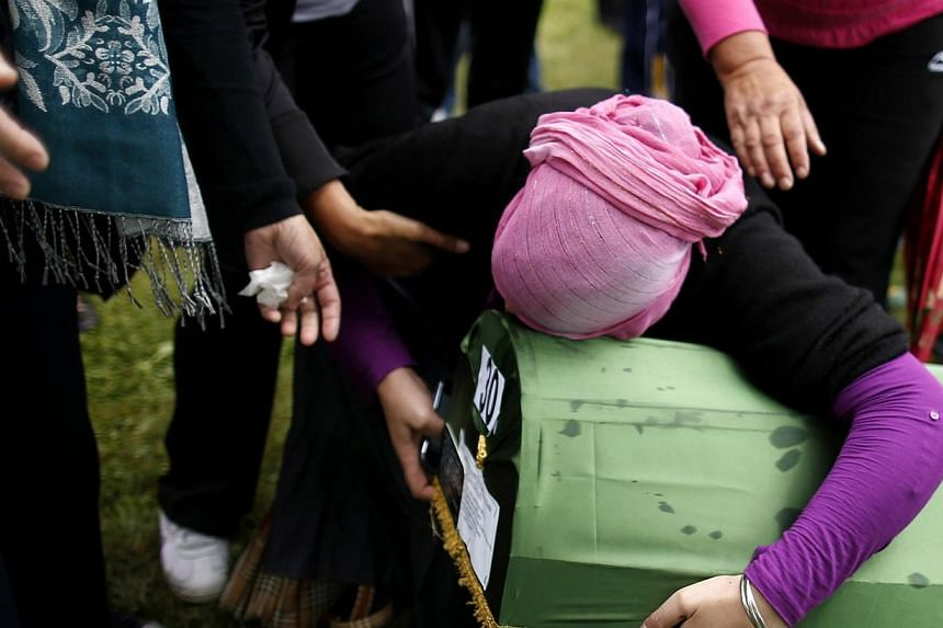 A Bosnian Muslim woman cries, holding the coffin of a relative, one of 175 newly identified victims from the 1995 Srebrenica massacre, at Potocari Memorial Centre, near Srebrenica on July 11, 2014. -- PHOTO: REUTERS