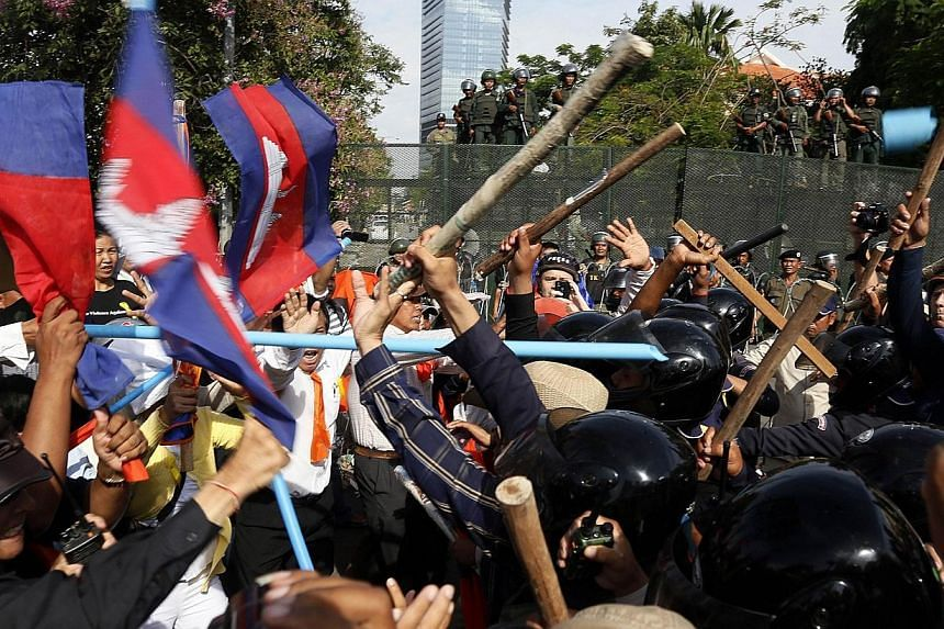 Cambodian security guards clash with demonstrators protesting for Freedom Park to open in Phnom Penh on July 15, 2014.A Cambodian court Wednesday, July 16, 2014, charged six opposition politicians with leading an insurrection during a protest t