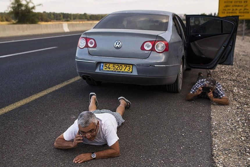 Israelis take cover on the side of a road as a siren sounds warning of incoming rockets outside the northern Gaza Strip on July 15, 2014. -- PHOTO: REUTERS