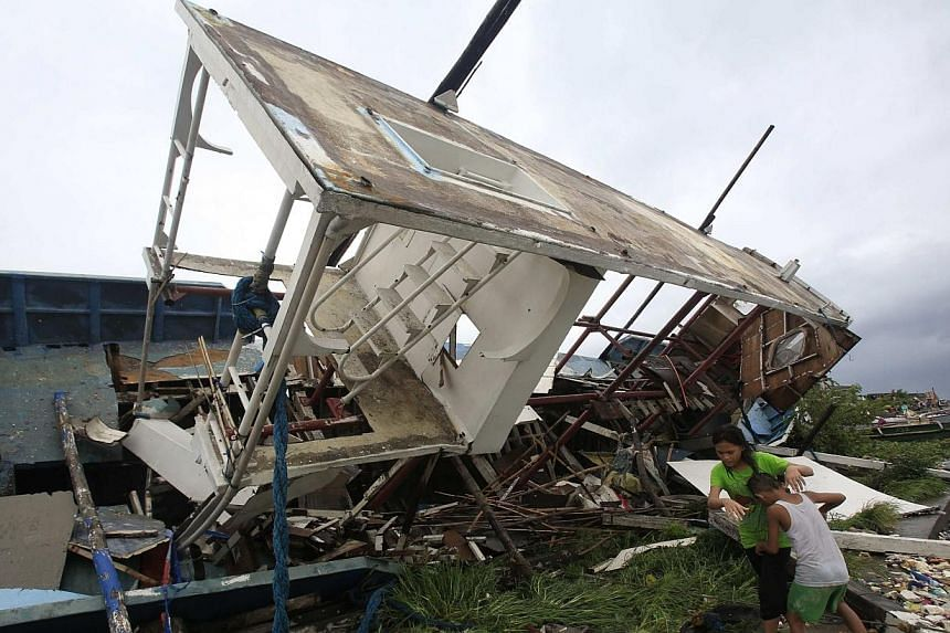 Residents walk beside a boat destroyed by strong winds brought by Typhoon Rammasun that battered the coastal bay of Baseco compound, metro Manila on July 16, 2014. -- PHOTO: REUTERS