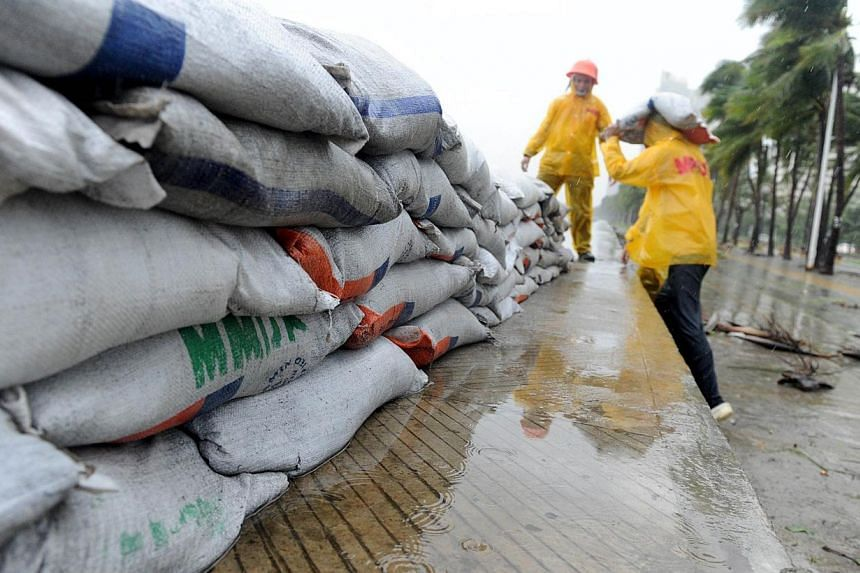 Workers pile sand bags along the sea wall of Roxas Boulevard as Typhoon Rammasun hit Metro Manila on July 16, 2014. -- PHOTO: AFP