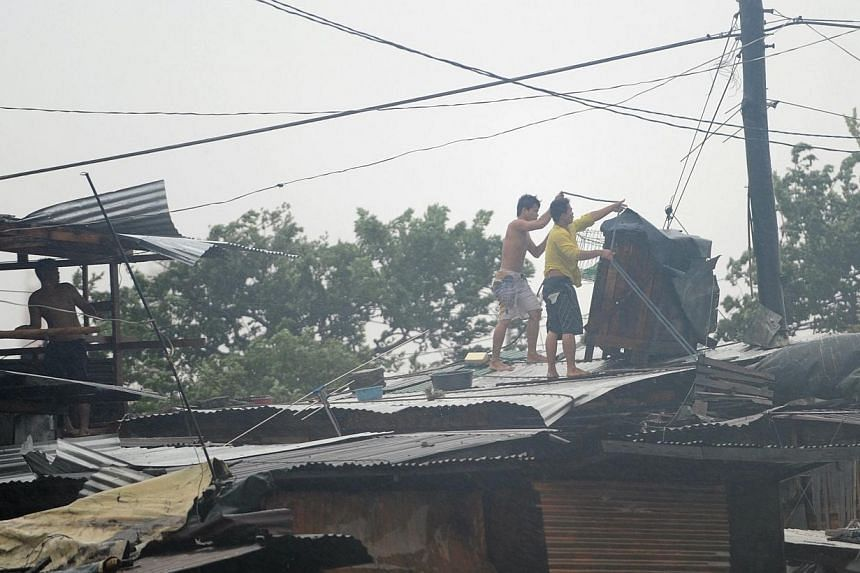 Residents try to fix the roofs of their homes in the wind and rain as Typhoon Rammasun barrels across Manila on July 16, 2014. -- PHOTO: AFP