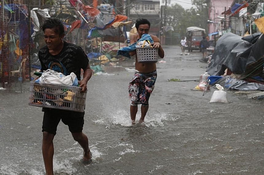 Residents carry their belongings as Typhoon Rammasun (locally named Glenda) hit the town of Imus, Cavite southwest of Manila on July 16, 2014. -- PHOTO: REUTERS