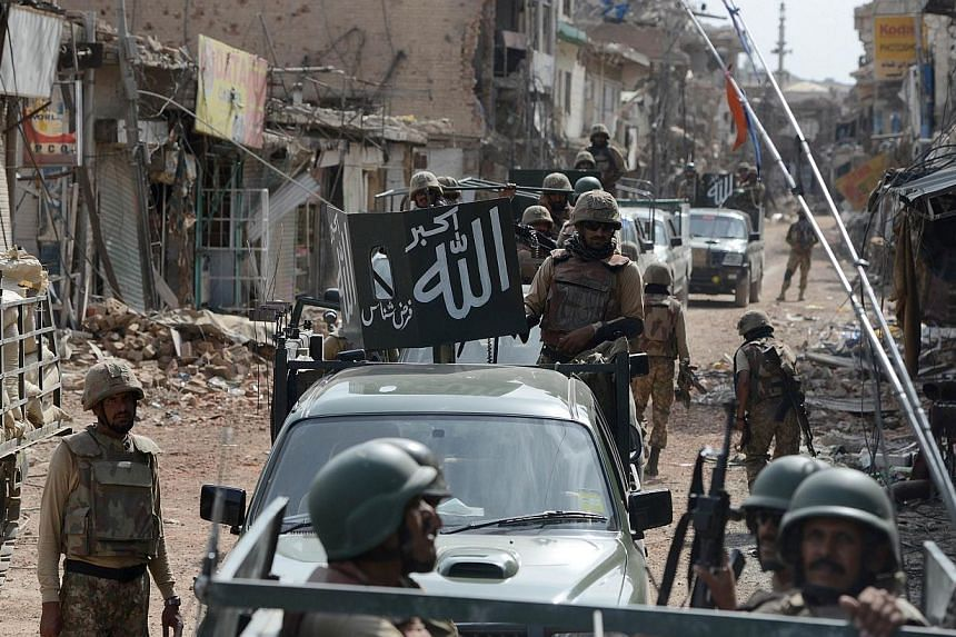Pakistani soldiers patrol through a destroyed bazaar during a military operation against Taliban militants, in the main town of Miranshah in North Waziristanon July 9, 2014.A US drone strike hit a suspected militant compound in Pakistan's