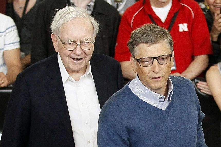 Berkshire Hathaway CEO Warren Buffett (left) and friend Bill Gates, founder of Microsoft, play table tennis at a Berkshire sponsored reception in Omaha, Nebraska on May 4, 2014 as part of the company annual meeting weekend.Warren Buffett this w