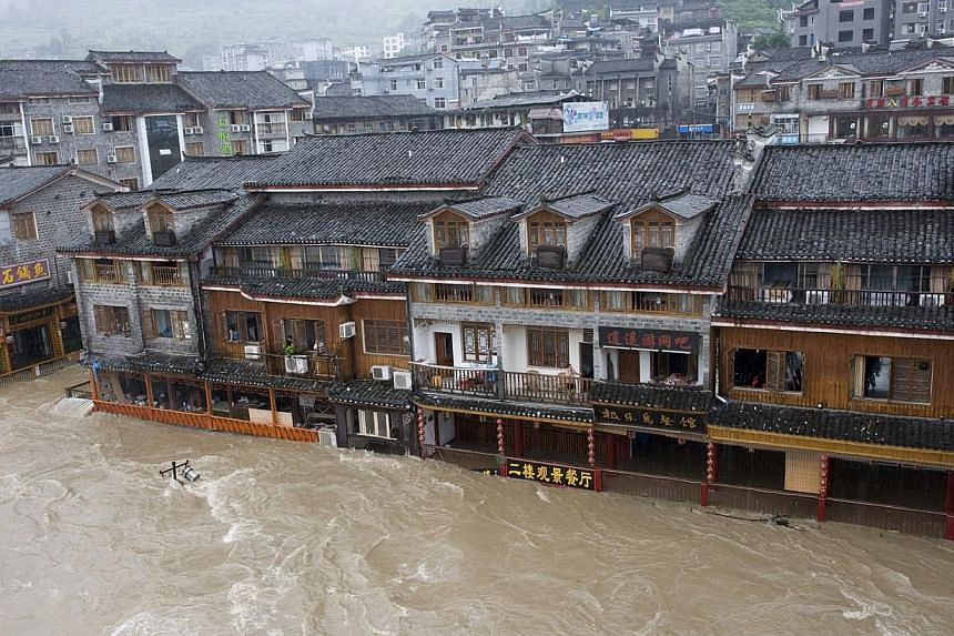 Floodwaters engulfing streets in the ancient town of Fenghuang, central China's Hunan province on July 15, 2014. -- PHOTO: AFP