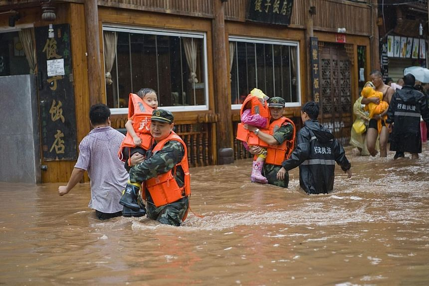 Rescuers helping victims on a street submerged in floodwaters in the ancient town of Fenghuang, central China's Hunan province on July 15, 2014. -- PHOTO: AFP