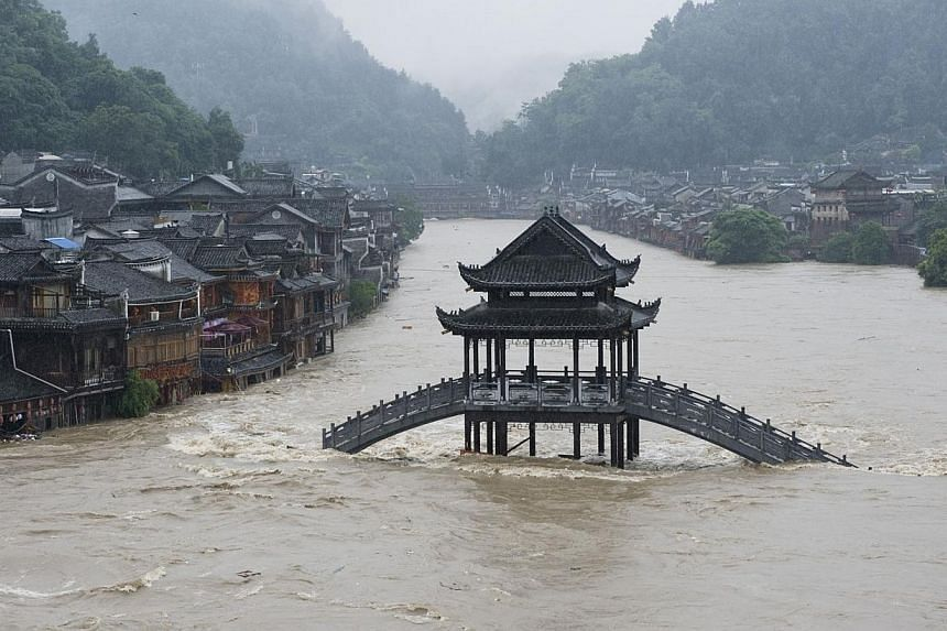 A bridge submerged in floodwaters in the ancient town of Fenghuang, central China's Hunan province on July 15, 2014. -- PHOTO: AFP