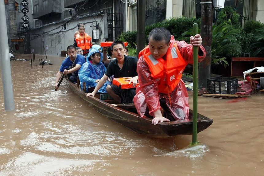 Rescuers evacuate residents and tourists with a boat on a flooded street of the ancient town as heavy rainfall hit Fenghuang county, Hunan province on July 15, 2014. -- PHOTO: REUTERS