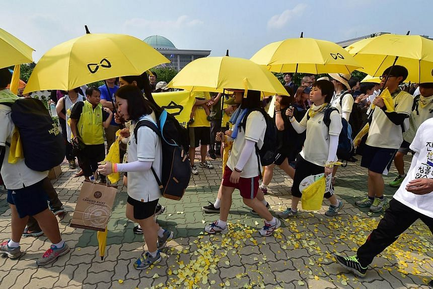 More than 30 student survivors of South Korea's ferry disaster marching with yellow umbrellas near Parliament in Seoul on July 16, 2014 to press demands by victims' relatives for an independent inquiry into the tragedy that claimed around 300 lives.