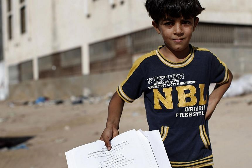 A Palestinian boy shows flyers dropped over Gaza City by the Israeli army urging residents to evacuate their home by 0500GMT, on July 16, 2014, in Gaza City.-- PHOTO: AFP