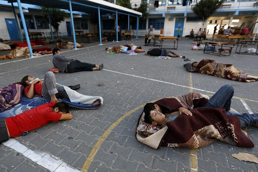 Palestinians sleep at the yard of a UN school in the northern Gaza Strip town of Beit Lahia early on July 16, 2014, after evacuating their houses near the border with Israel. -- PHOTO: AFP