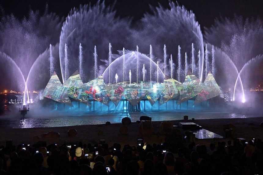 Visitors watch a new night show called Wings Of Time, featuring majestic water effects, fireworks and a light projection at Sentosa's Siloso Beach in Singapore on June 24, 2014. Wings Of Time officially opened on Wednesday. -- PHOTO: AFP