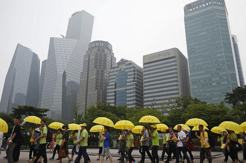 People holding yellow umbrellas in support of victims of the mid-April Sewol ferry disaster, carry boxes containing signatures of South Koreans petitioning for the enactment of a special law after the disaster, as they march towards the National Asse