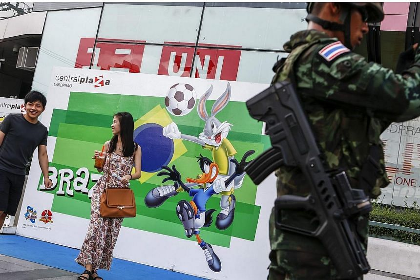 A Thai soldier stands next to a billboard to promote the Brazil World Cup 2014 as passers-by walk past outside a shopping mall in Bangkok on June 23, 2014.Police in Thailand said on Tuesday, July 15, 2014, that they had arrested 5,064 people fo
