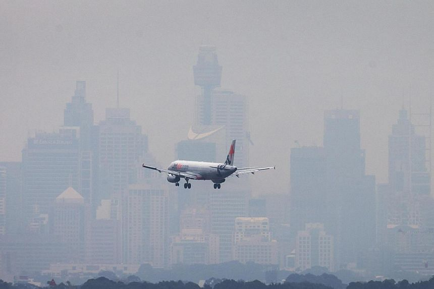 An Australian commercial aircraft prepares to land in the haze at Sydney's International Airport on July 15, 2014. -- PHOTO: REUTERS