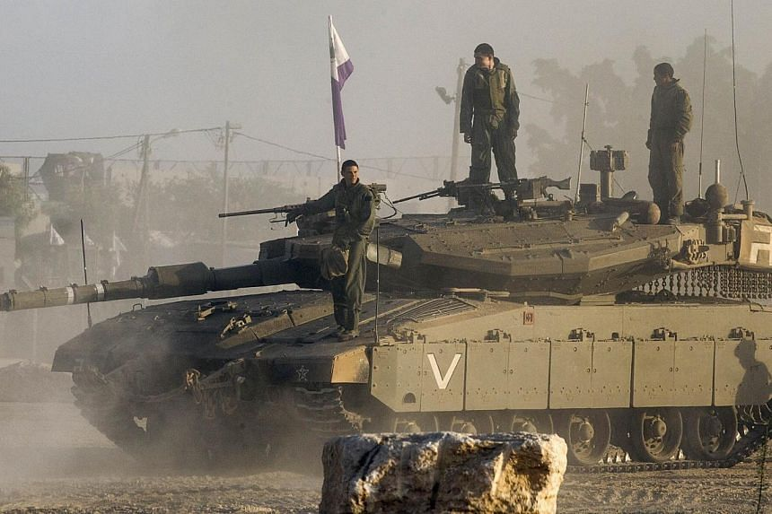 Israeli soldiers stand on their Merkava tank on July 17, 2014 at an army deployment area near Israel's border with the Gaza Strip.An Israeli official said on Thursday, July 17, 2014, that Israeli senior representatives at talks in Cairo had acc