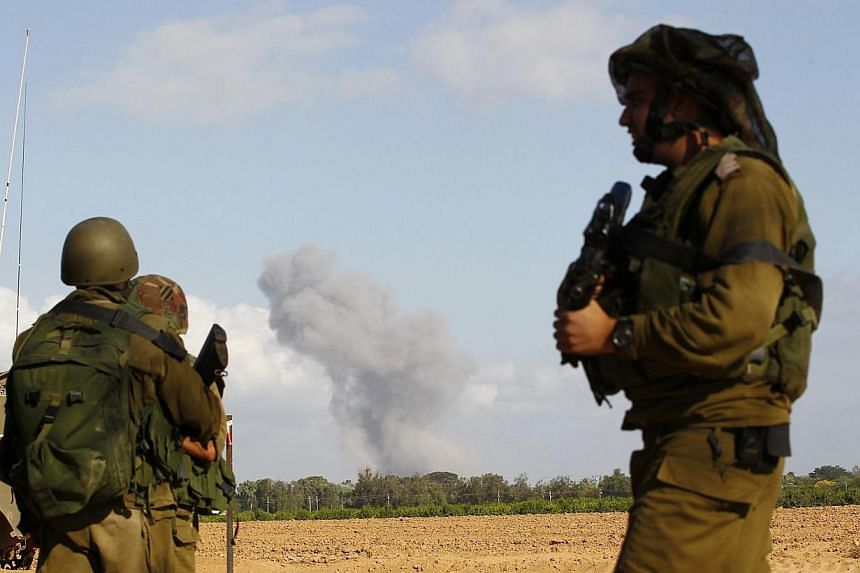 Israeli soldiers stand guard outside the southern Gaza Strip, as smoke is seen in Gaza, before the start of a five-hour ceasefire on July 17, 2014.Three mortar shells fired from Gaza hit southern Israel on Thursday, July 17, 2014, the army said