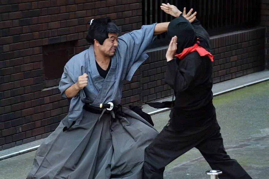 Members of pantomime group Gabez clad in a samurai (right) and ninja (left) costumes performing at Asakusa shrine in Tokyo during a press preview for the new bus tour to enjoy ninja acts on the street and the ancient shrine on July 16, 2014. Jap