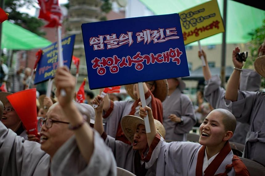 "Nuns hold placards reading 'you rock' as they shout support for performers at a Buddhist prayer competition at the Jogyesa temple in Seoul on July 17, 2014. South Korea's top Buddhist organisation held an experimental ""prayer competition"" on Thu"