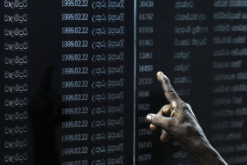 Sri Lankans read through names of fallen soldiers on a memorial for those who died in the decades-long conflict against the Tamil Tigers, during National War Hero's Day in Colombo on May 19, 2014. Sri Lanka announced on Thursday,July 17, 2014, a