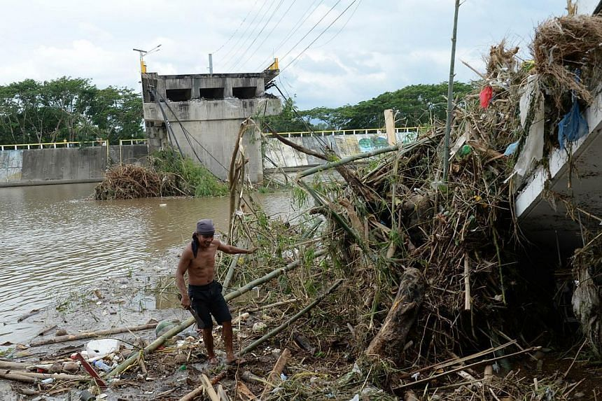 A resident collects bamboo poles washed near a bridge destroyed at the height of Typhoon Rammasun in Batangas City, south-west of Manila on July 17, 2014, a day after it barrelled into the capital Manila and nearby provinces. -- PHOTO: AFP