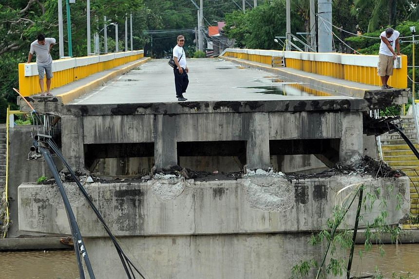 Residents survey a bridge destroyed at the height of Typhoon Rammasun in Batangas City, south-west of Manila on July 17, 2014, a day after it barrelled into the capital Manila and nearby provinces. -- PHOTO: AFP
