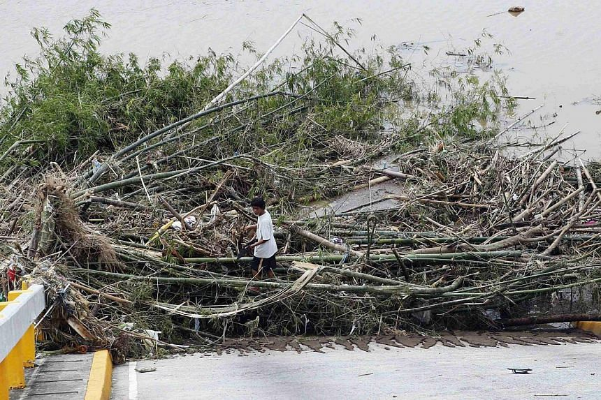 A worker prepares to clear debris on a bridge destroyed during the onslaught of Typhoon Rammasun, (locally named Glenda) in Batangas city south of Manila on July 17, 2014. -- PHOTO: REUTERS