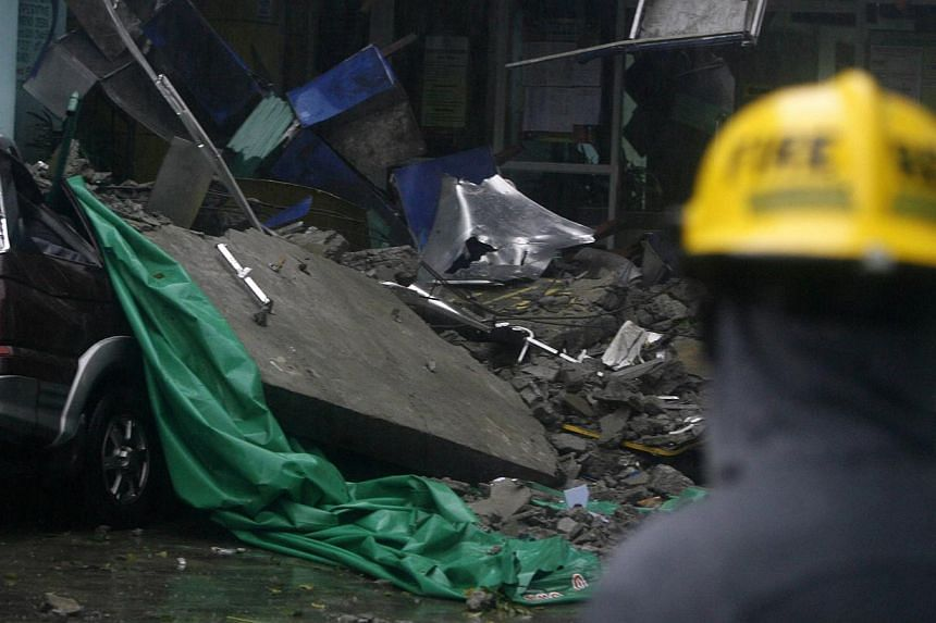 A rescuer looks at a collapsed government village hall due to the onslaught of Typhoon Rammasun, (locally named Glenda) in Quezon city, Metro Manila on July 16, 2014. -- PHOTO: REUTERS